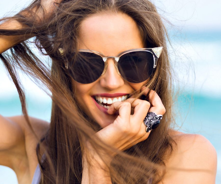 Blissful brunette woman wears stylish ring laughing while posing at sea. Close-up portrait of tanned girl in black sunglasses playing with her dark hair on blur background.