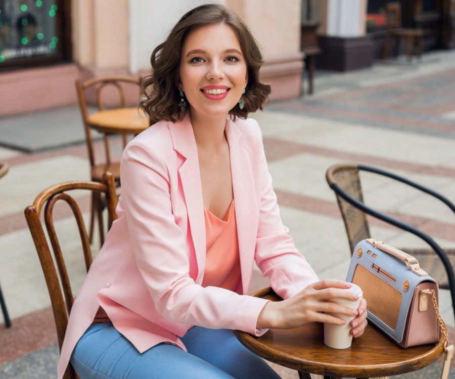 portrait of stylish smiling lady sitting at table drinking coffee in pink jacket summer style trend, blue handbag, accessories, street style, women fashion